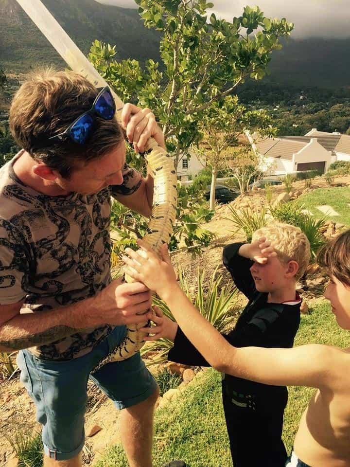 Children touching a puff adder
